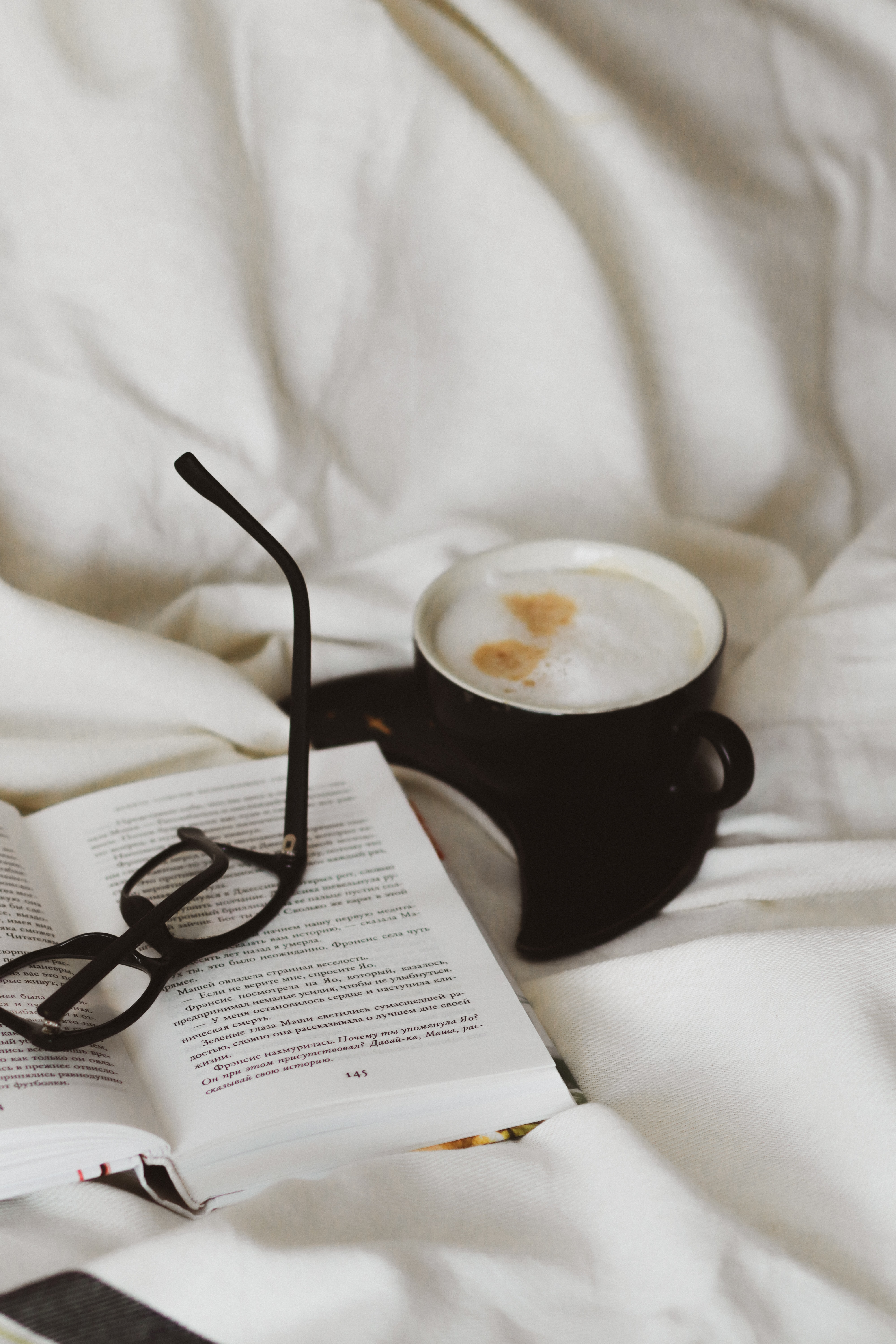 A book, a glasses, and a cup of coffee